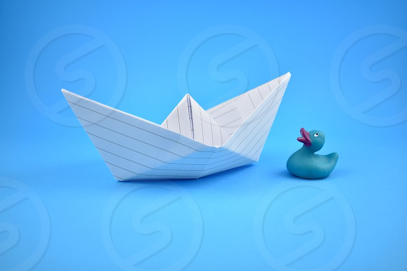 Paper boat and rubber duck. Paper boat on a blue background. Blue background with boat and rubber duck. photo