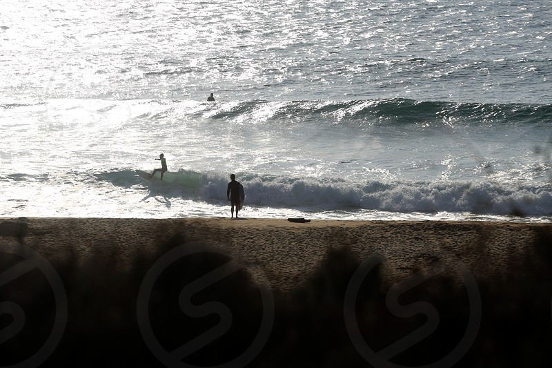 Surfers at the beach and dusk photo
