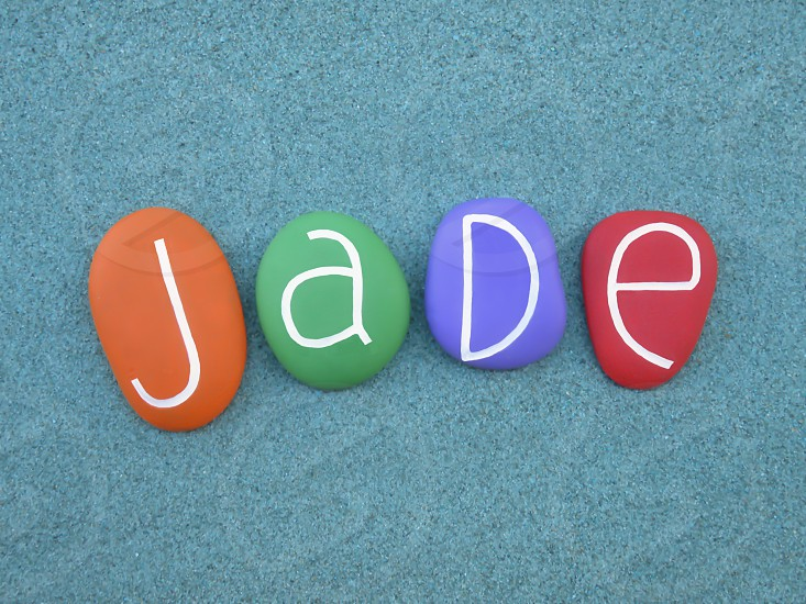 Jade  given name derived from the ornamental stone jade composed with multi colored stone letters over green sand                                 photo