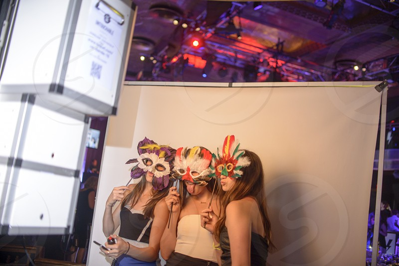 3 girls covering their faces with masks at the ball photo
