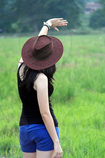 selective focus photography woman in black tank top and blue denim shorts with brown cowboy while hat raising left hand during daytime photo