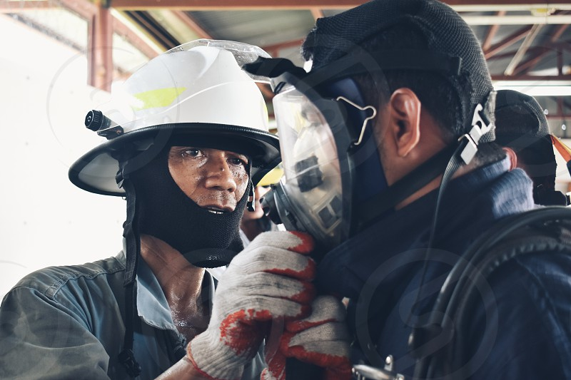A fire fighter helping another fire fighter with his mask photo