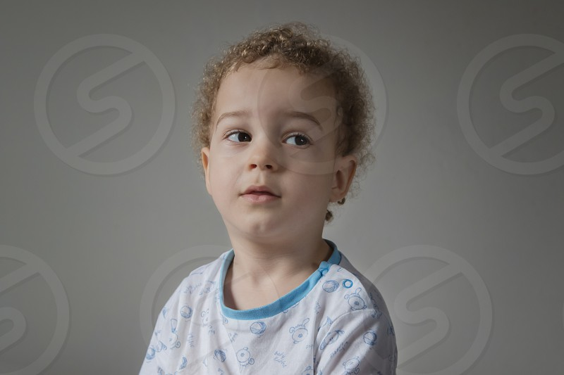 Adorable two years old kid in soft pyjamas with blue and withe colours in sunny kids room. Child's sleep concept soft focus. photo
