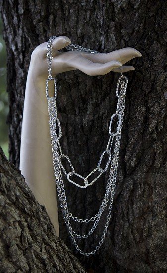 A silver necklace draping from a hand that seems to growing out of tree. photo