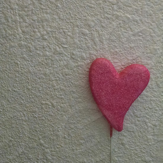 Pink heart on a white wall photo