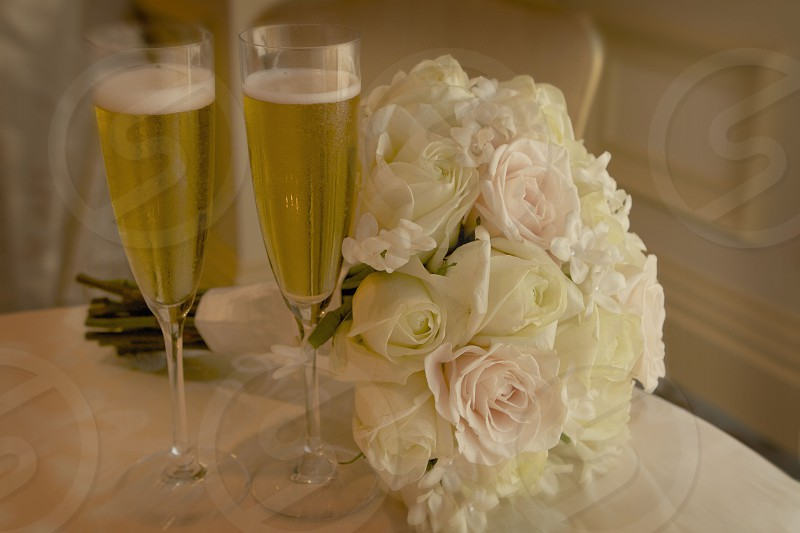 2 wine glass fully filled near bundle of white flower photo