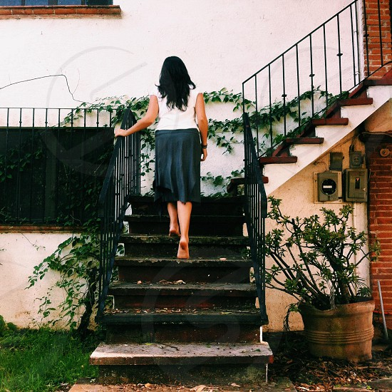 woman wearing a black skirt climbing a staircase photo