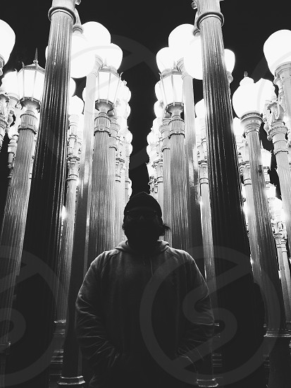 greyscale photography of man in pullover hoodie standing in between street lamp posts photo