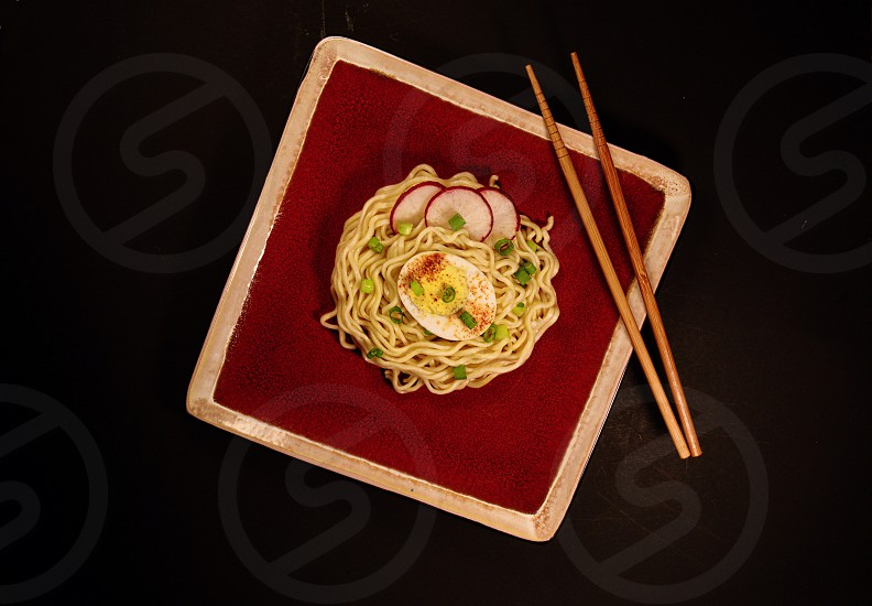 Ramen Noodles with hardboiled egg green or spring onions and radish on red plate with chopsticks photo