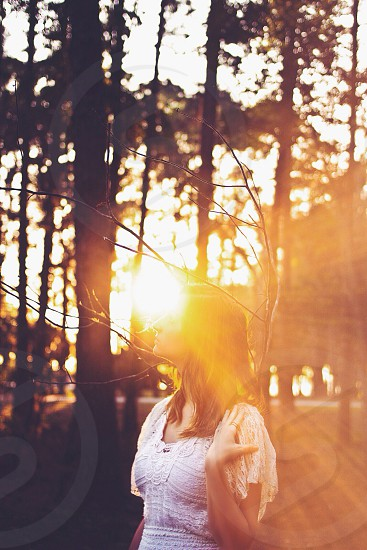 woman in white dress standing on forest in sunrise photo