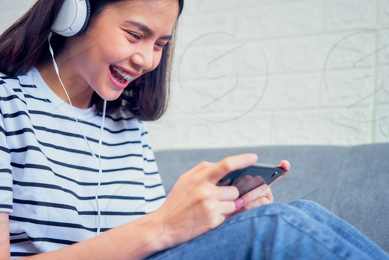 Excited young Asian woman sitting on sofa wear white headphone on the head and playing games on smartphone in the living room at home. photo