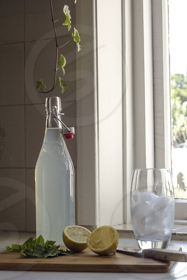Lemon and mint ingredients and bottle with an ice filled glasss  photo