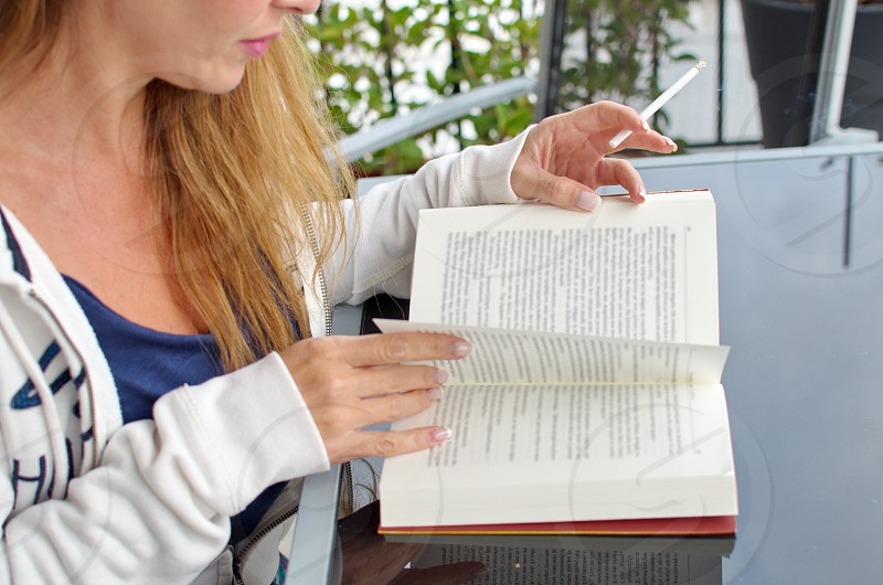 woman reading a book with a cigarette in her hand photo