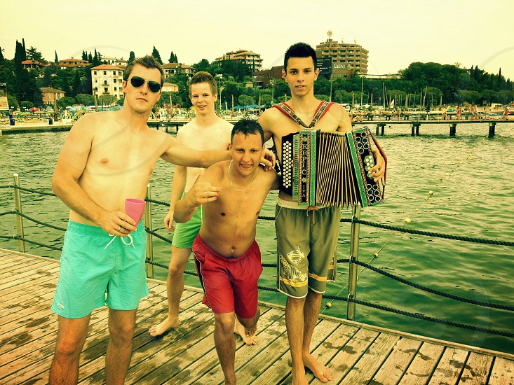 man holding musical instrument near the 3 man photo