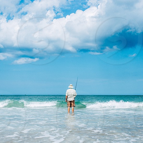 man in white bucket hat standing on beach holding fishing rod with waves crashing photo