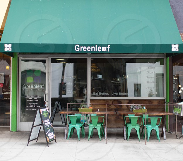 4 empty seats outside greenleaf cafe during daytime photo