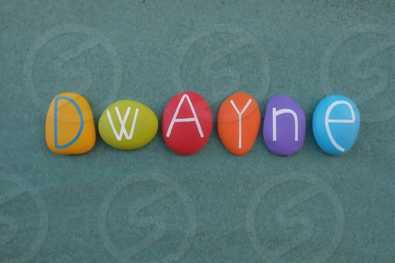 Dwayne male given name composed with multi colored stone letters over green sand photo