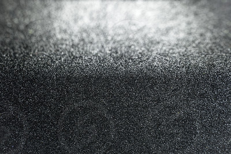 Black glitter background with selective focus on surface texture with defocused area in background photo