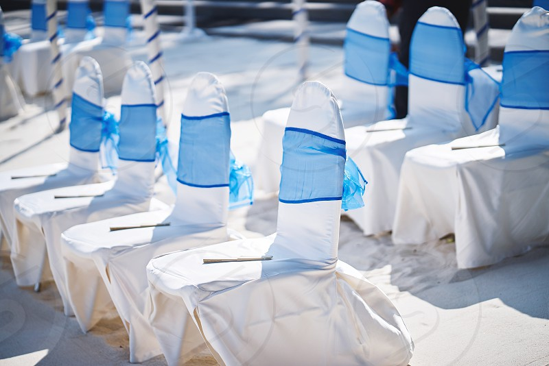 The beach wedding venue preparation before ceremony with white chairs and blue sash organza stripe photo
