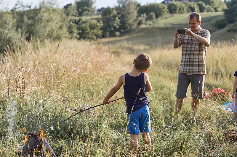 Man taking a photo his son roasting marshmallow over a campfire. Family spending time together on a meadow close to nature. Candid people real moments authentic situations photo