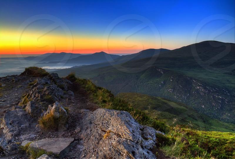 green rolling hills under sunset photo