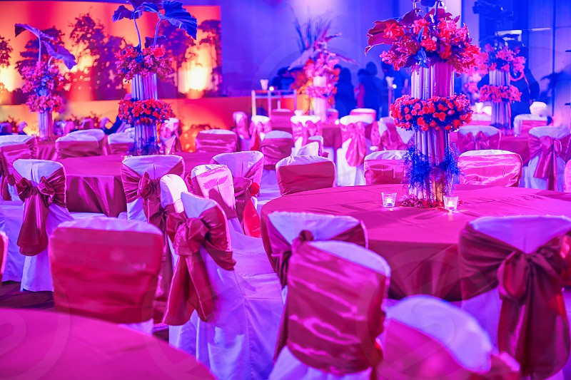 Indian wedding reception dinner table chairs settings decorating with vase of flower Colorful LED lighting decoration for traditional indian sangeet night party photo