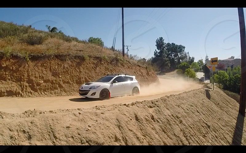 Cliff hanging photo of a Mazda Speed 3 Drifting. photo