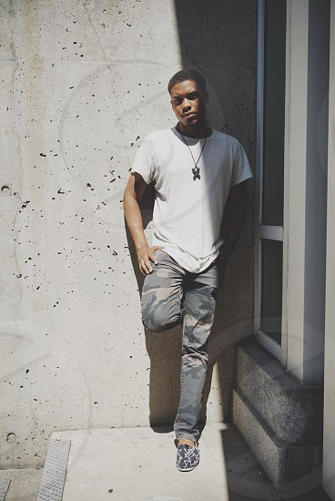 man wearing white t shirt and grey black and brown camouflage jeans leaning on wall during daytime photo
