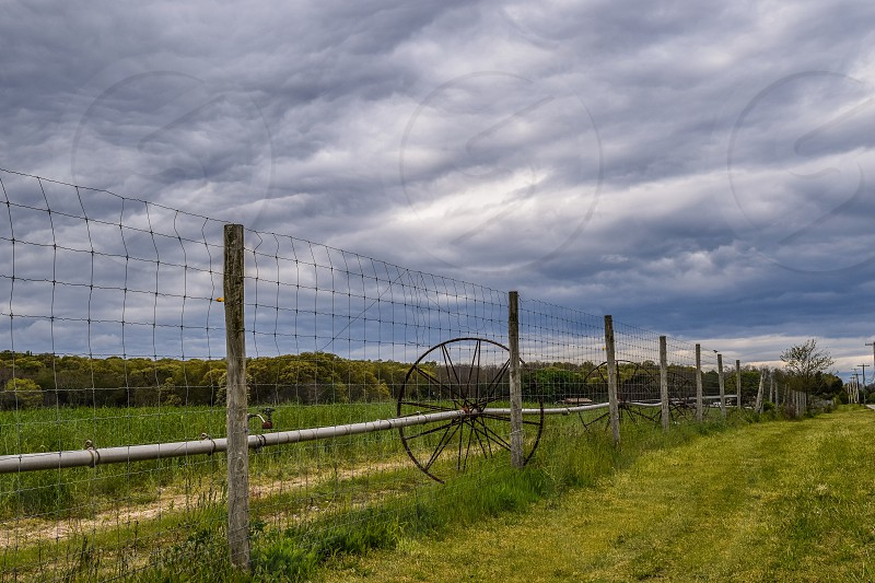 brown wooden framed wire fence with black steel wheel turbine on green grass field photo