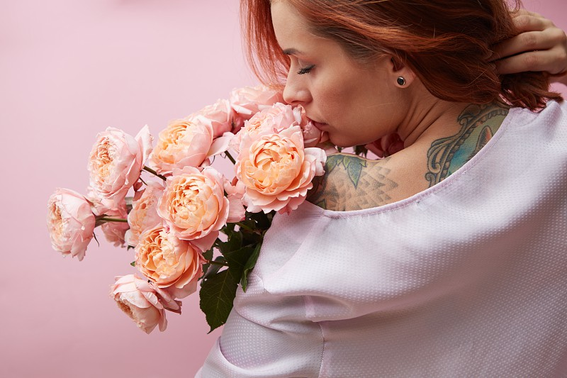 Beautiful pink roses of a media on a shoulder of a red-haired girl on a pink background. Valentine's Day Mother's Day photo