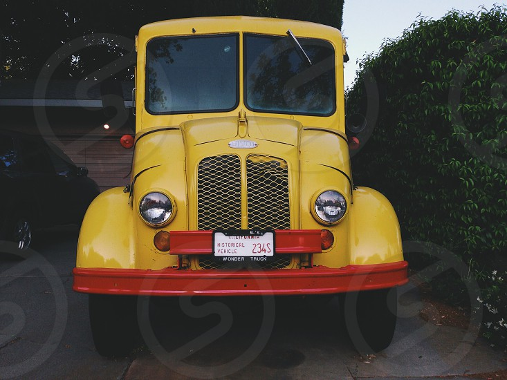 yellow and red vintage historical vehicle wonder truck parked in driveway near green hedge photo