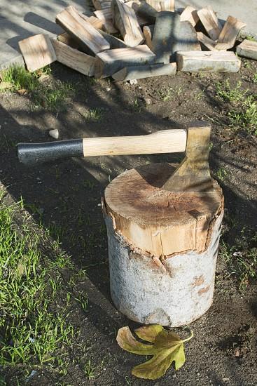 Ax chopping wood on chopping block. Autumn leafs photo