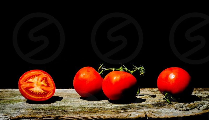 tomatoes red art black background close-up multiple fresh organic farm photo