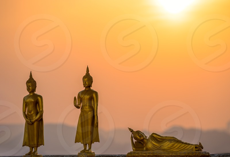 Golden small statues of Buddha in the Wat Tham Suea Tiger cave temple on the background of the silhouettes of the mountains in Thailand at orange sunset photo
