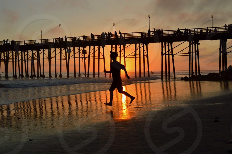 silhouette of man running on the beach by the pier photo