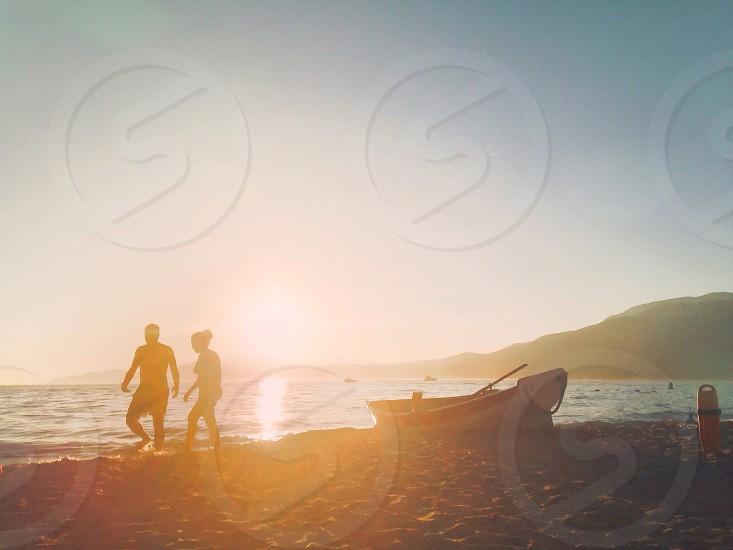 man and woman walking on shore near boat photo
