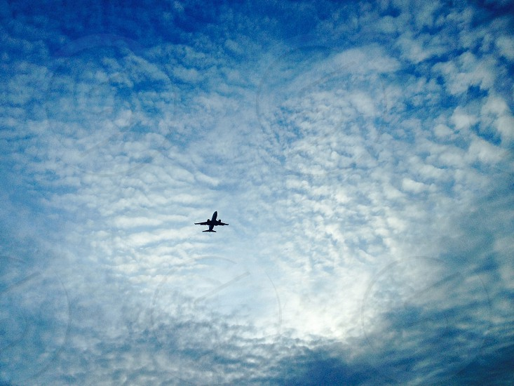 airliner flying under white clouds in a blue sky photo
