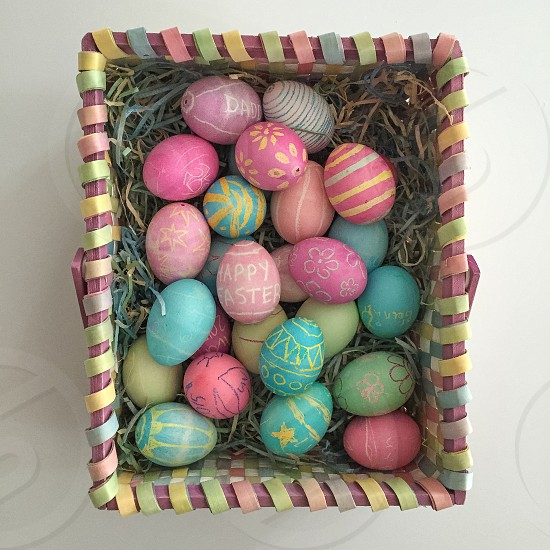 pink blue and yellow eggs in brown wooden container photo