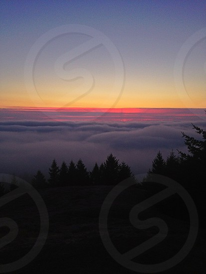 sunset peaking over clouds panoramic photography photo