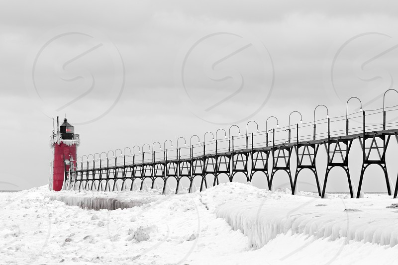 A red lighthouse covered in snow and ice photo