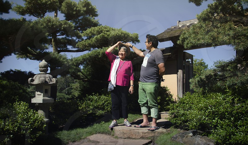 Authentic Family Life in the Philippines Filipino mother and son laughing bonding outside Asian Zen garden photo