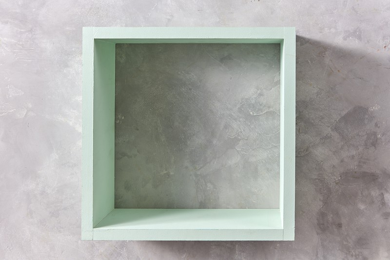square green wooden wall isolated on gray concrete wall with copy space. Product display template photo