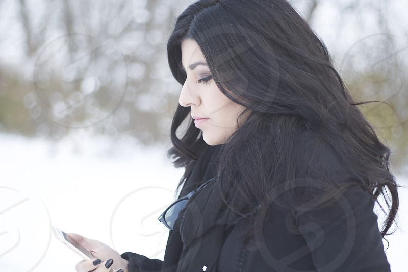 close up photo of woman wearing black coat holding a white smartphone during winter time photo