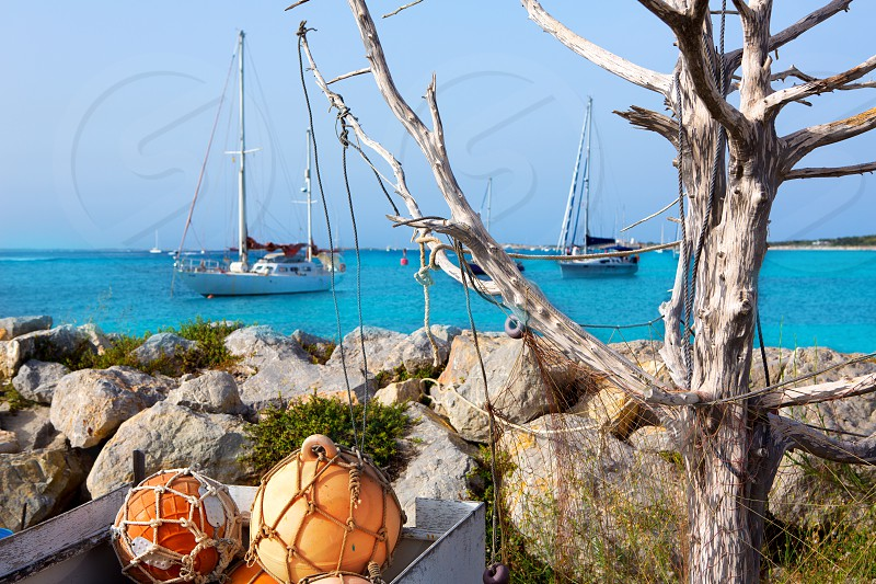 Aqua mediterranean in formentera with fishing buoys and sailboats photo