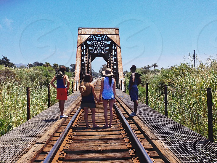 woman in  white tank top standing on railroad near man in blue shorts photo