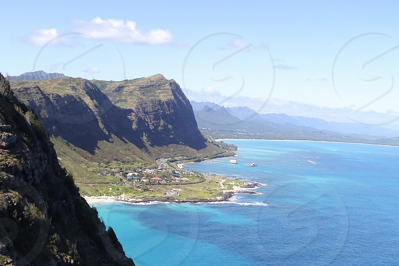 landmark photography of mountain beside beach under blue and white sky during day time photo