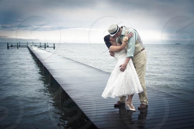 men kissing a woman on sea dock photo
