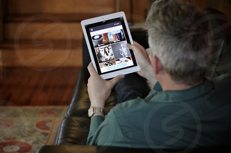 Man reclined on a sofa looking at a tablet photo