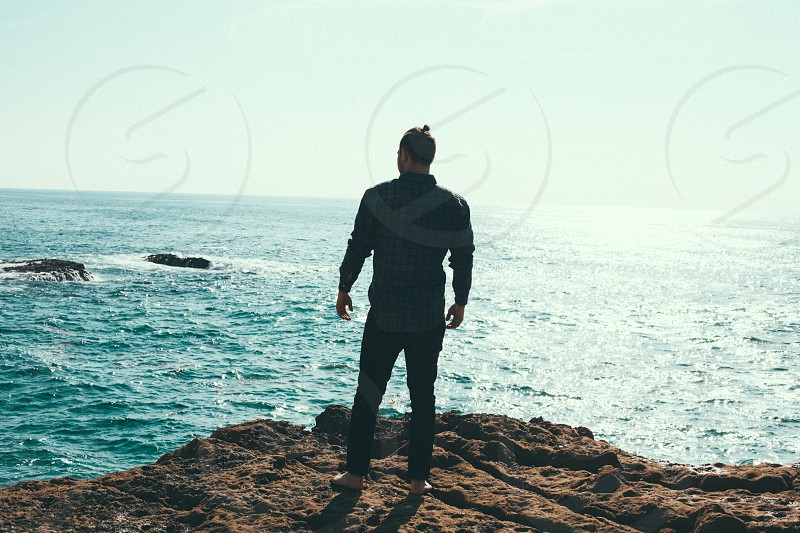 man standing on brown land near body of water under blue sky photo