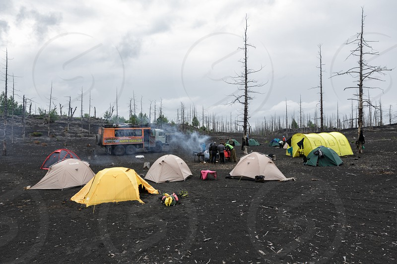 KAMCHATKA PENINSULA RUSSIA - June 25 2014: Tourist campground in Dead Wood on volcanic slag and ash eruptions Tolbachik Volcano - consequence of catastrophic eruption of volcano during on 1975-1976. photo